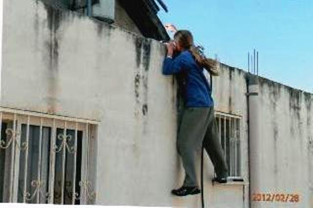 נער מנסה להוריד כדור שהועף לגג ביתו של רחום (צילום: הרצל רחום)