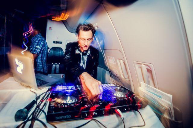 """ד'י.ג'יי של """"טומורולנד"""" בתא הנוסעים מפעיל בחי על מערכות המוסיקה הממוחשבות בגובה 30 אלף רגל. צילום יח""""צ"""